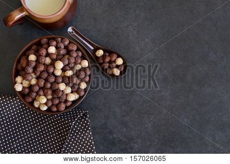 Healthy breakfast. Chocolate breakfast cereal with milk on a black background.