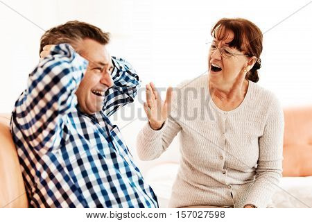 Senior couple have conflict in living room.