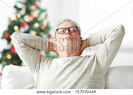 old age, holidays, comfort and people concept - senior man in glasses relaxing on sofa at home over christmas tree background