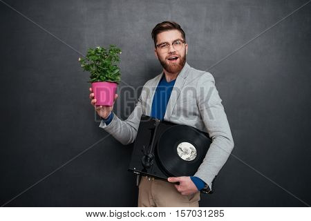 Smiling bearded young businessman in glasses holding flowers in pot and turntable