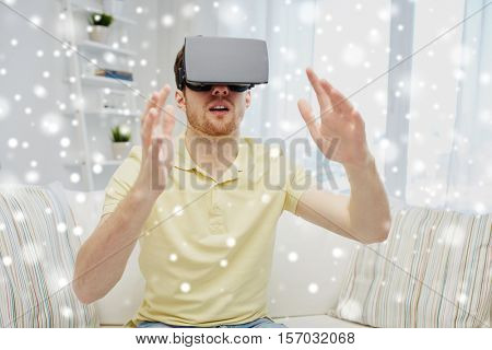 technology, augmented reality, gaming, entertainment and people concept - happy young man with virtual headset or 3d glasses playing video game over snow
