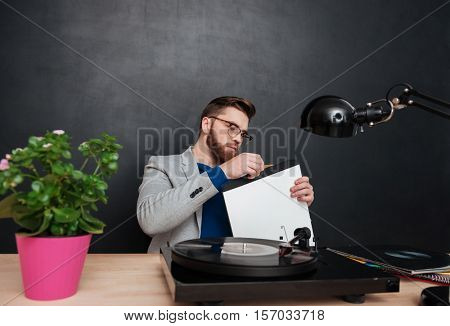 Focused bearded young businessman using turntable and vinyl record