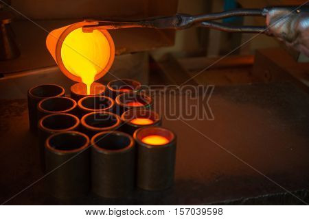 Pouring melted gold in the metal form at a factory