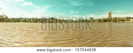 Day at park with a lake green vegetation and some buildings of the city on background. Scene reflected on water. Panoramic photo at Parque das Nações Indígenas in Campo Grande MS Brazil.