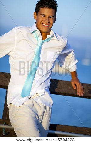 Young man on a pier in a tie at sunset