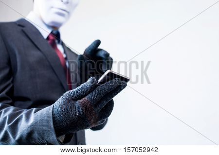 Business man in white mask wearing gloves and using mobile phone - fraud hacker theft cyber crime concept