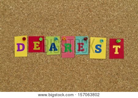 Dearest word written on colorful sticky notes pinned on cork board.
