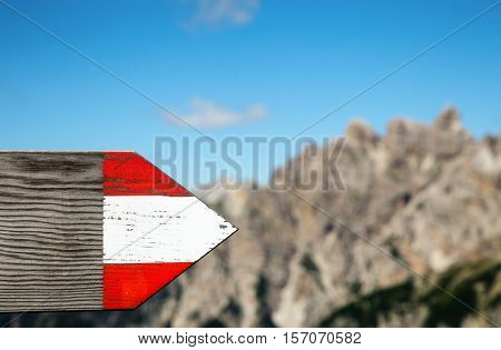 Wooden directional sign on a hiking route in Dolomite Alps Italy with mountains in background