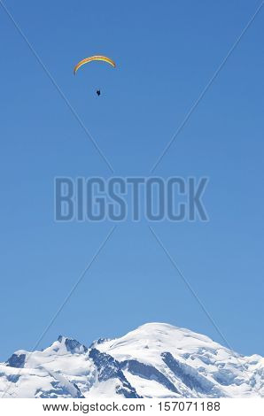 Paragliding flying over Mont Blanc Massif, in the background is Mont Blanc peak, Alps, Chamonix, France