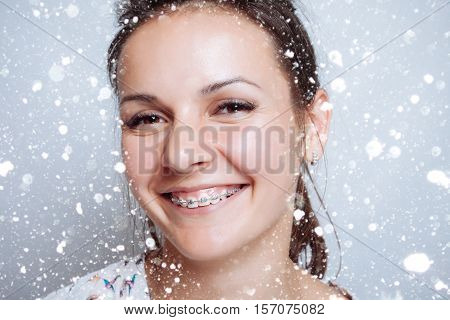 woman portrait dental braces natural. concept of medicine and dentistry. beautiful white teeth. beauty people advertisement winter and health concept . over snow on gray background