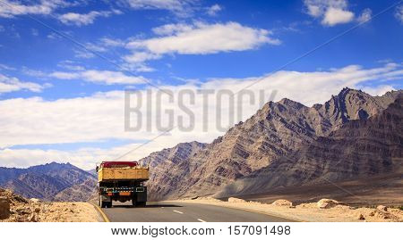 A truck driving down the road in Ladakh region of Kashmir, India