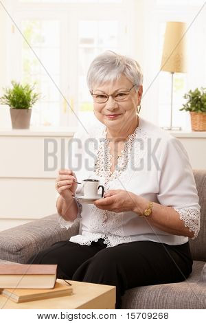 Portrait of senior woman sitting on sofa drinking coffee at home, looking at camera smiling.?
