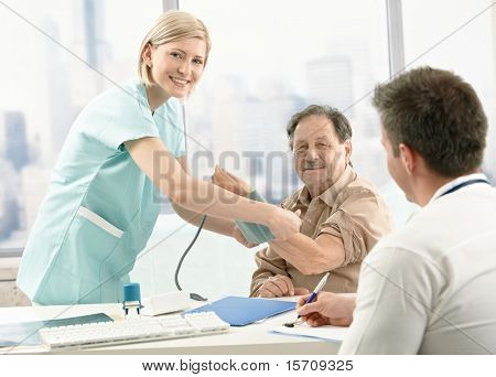 Old patient at examination in doctor's office, smiling nurse measuring blood pressure.?