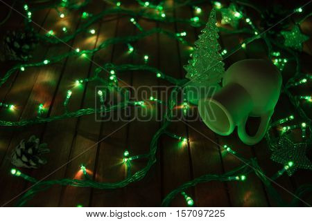 Jar and fir tree with garland and pinecone on red wooden background