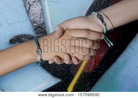 Elche, Spain. October 23, 2016: Two hands of friends caught on a background painted with graffiti.