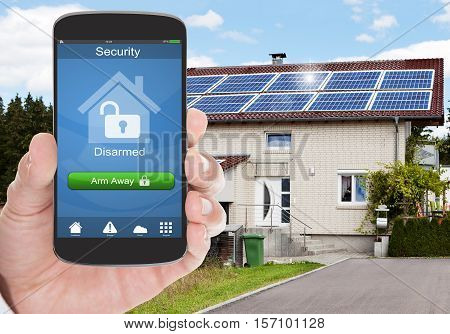 Close-up Of Person Hand Holding Mobile Phone With Home Security System Outside The House