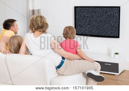 Family Sitting On Couch Watching Television Together Showing No Signal At Home