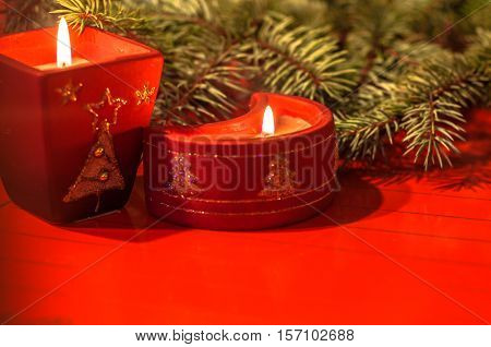 Advent: Christmas themed decorative red candles on red background with pine branch