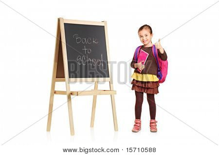 A child next to a school board holding book and showing thumb up isolated on white background