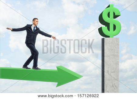 A businessman walking on a green arrow, trying to balance himself and get to a green big dollar sign situated on a high gray pedestal on the sky background. Make profits. Business difficulties. Overcoming obstacles.