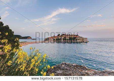 Sveti Stefan island and beach near Budva, Montenegro on Adriatic coast. Evening view of Adriatic sea, St. Stefan luxury fortificated village and private beach.