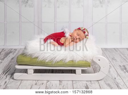 beautiful newborn in red romper sleeping on sleigh cot with white fluffy blanket