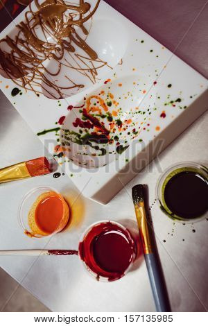 Close-up of colored mould and paintbrush in kitchen