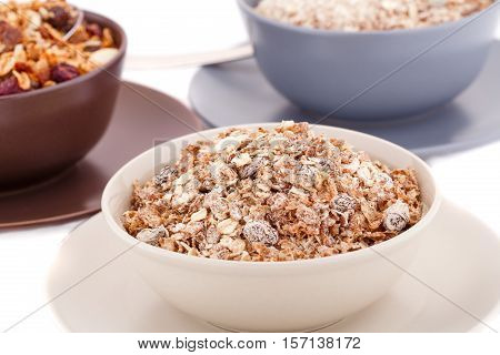 Muesli in the bowls on white background.