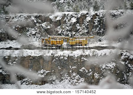 Yellow mining machines on the slopes of a granite quarry in the snowy winter day
