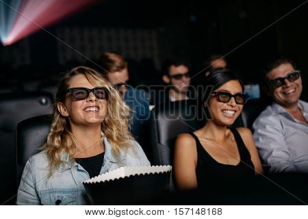 Group of friends watching 3d movie in cinema. Men and women watching 3d film in theater.