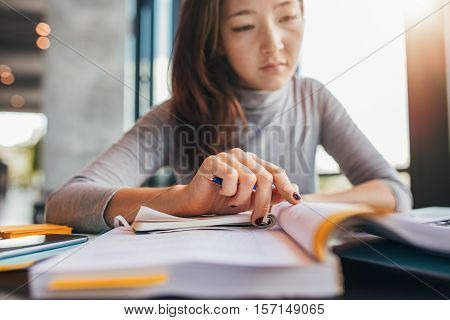 Close up image of a young female student doing assignments in library. Asian woman taking notes from textbooks.