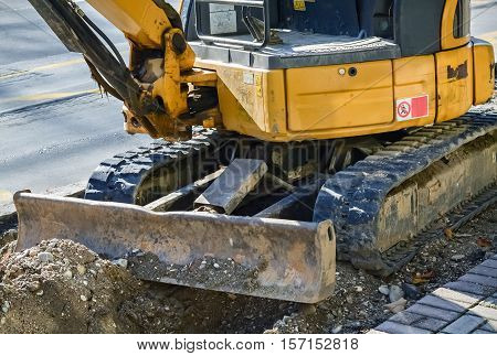 Closeup of a small yellow bulldozer during the reconstruction on the road