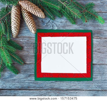 Christmas card with christmas natural decorations. Greeting card for the Christmas holidays . Spruce branches. Empty paper sheet on rustic table from above. Blank sheet for the greetings.