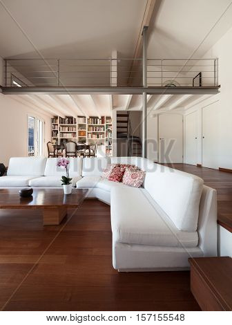 Interiors, comfortable living room of a loft, white divans