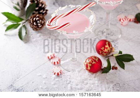 Peppermint martini cocktail with coconut flakes rim and candy cane