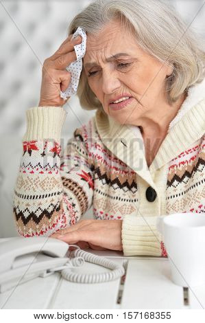 Portrait of stressed senior woman with handkerchief and phone