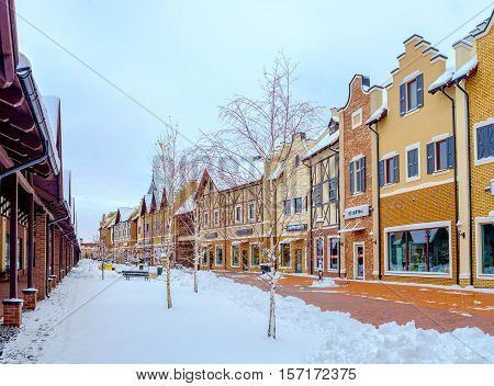 KIEV UKRAINE - NOVEMBER 11 2016: The brick stepped gable houses of Dutch Revival style shopping city look great in white cover of snow on November 11 in Kiev.