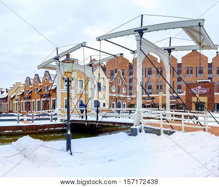 KIEV UKRAINE - NOVEMBER 11 2016: The white wooden drawbridge with chains was built as the visitor attraction in Dutch Revival style shopping city on November 11 in Kiev.