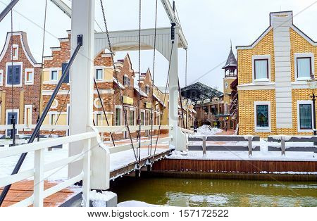 KIEV UKRAINE - NOVEMBER 11 2016: The view on the Dutch houses of the shopping neighborhood through the wooden constructions and chains of the drawbridge on November 11 in Kiev.