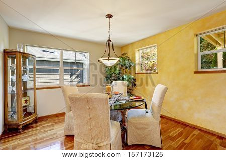 Interior Of Dining Room With Yellow Wall And Hardwood Floor.