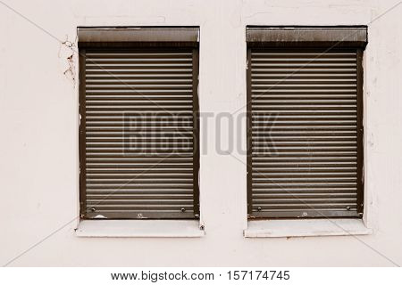Wall with two closed using roller-blind windows. Office in bad block.