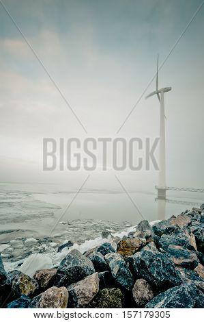 modern white wind turbine for generation of renewable electricity in Dutch winter landscape along the IJsselmeer