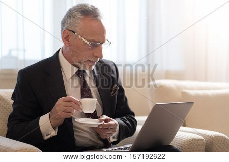 Involved in the process. Concentrated aged bearded businessman holding a cup of coffee and sitting in the hotel while looking at the laptop and wearing glasses