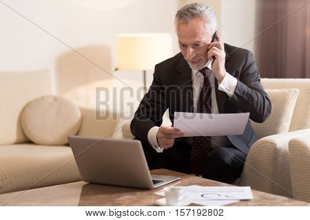 Delighted from the conversation. Smiling delighted bearded businessman talking on the phone and sitting in the hotel in front of the laptop while working with papers and expressing excitement