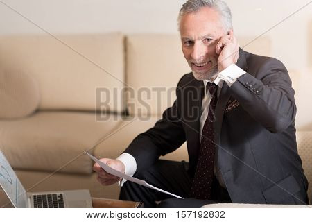 Pleasant conversation. Smiling cheerful bearded businessman talking on the phone and sitting in the hotel in front of the laptop while working with papers and expressing excitement