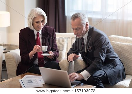 Working together. Pleasant bearded aged businessman looking and pointing on the laptop and sitting in the hotel while working on the project with his colleague and expressing interest