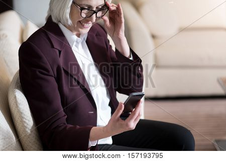 I getting acquainted with modern technologies. Pleasant charming aged businesswoman holding the phone and her glasses while sitting in the office and looking at the mobile