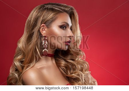 Beauty woman face with beautiful make-up colors. Blond hair wavy hair jewelry clear skin beautiful face. Portrait shot in studio on a red background.