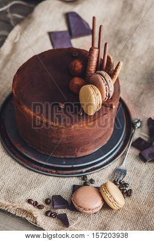 Chocolate cake covered with cocoa powder and decorated with cookies