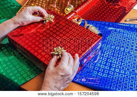Hands of senior woman decorating wrapped gift